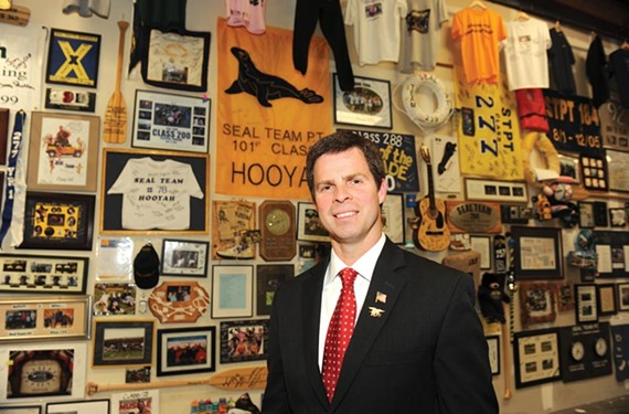 John McGuire, owner of SEAL Team Physical Training, in front of his tribute wall in the company's offices on Dabney Road. - SCOTT ELMQUIST