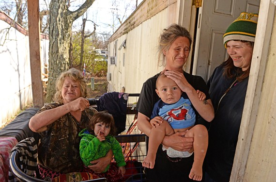 Joyce Elkins, Connie Butler and Ada Southall sit on the porch of their trailer with Alliyah Southall and Alberto Rivera. They live together in the trailer park behind Luis Pardo's tire shop. - SCOTT ELMQUIST