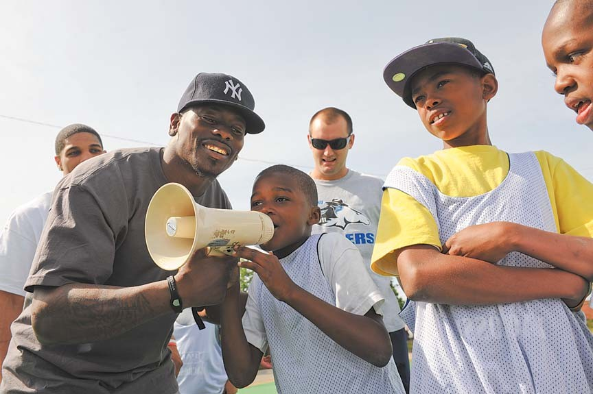 Junior Rosegreen, a former star at Auburn University, finally offers the bullhorn to a young player at the Police Athletic League football camp in mid-April. - SCOTT ELMQUIST