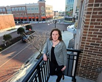 Katelyn Melo, who commutes daily to her job downtown from West Broad Village, relaxes on the balcony of her apartment overlooking Gathering Place.