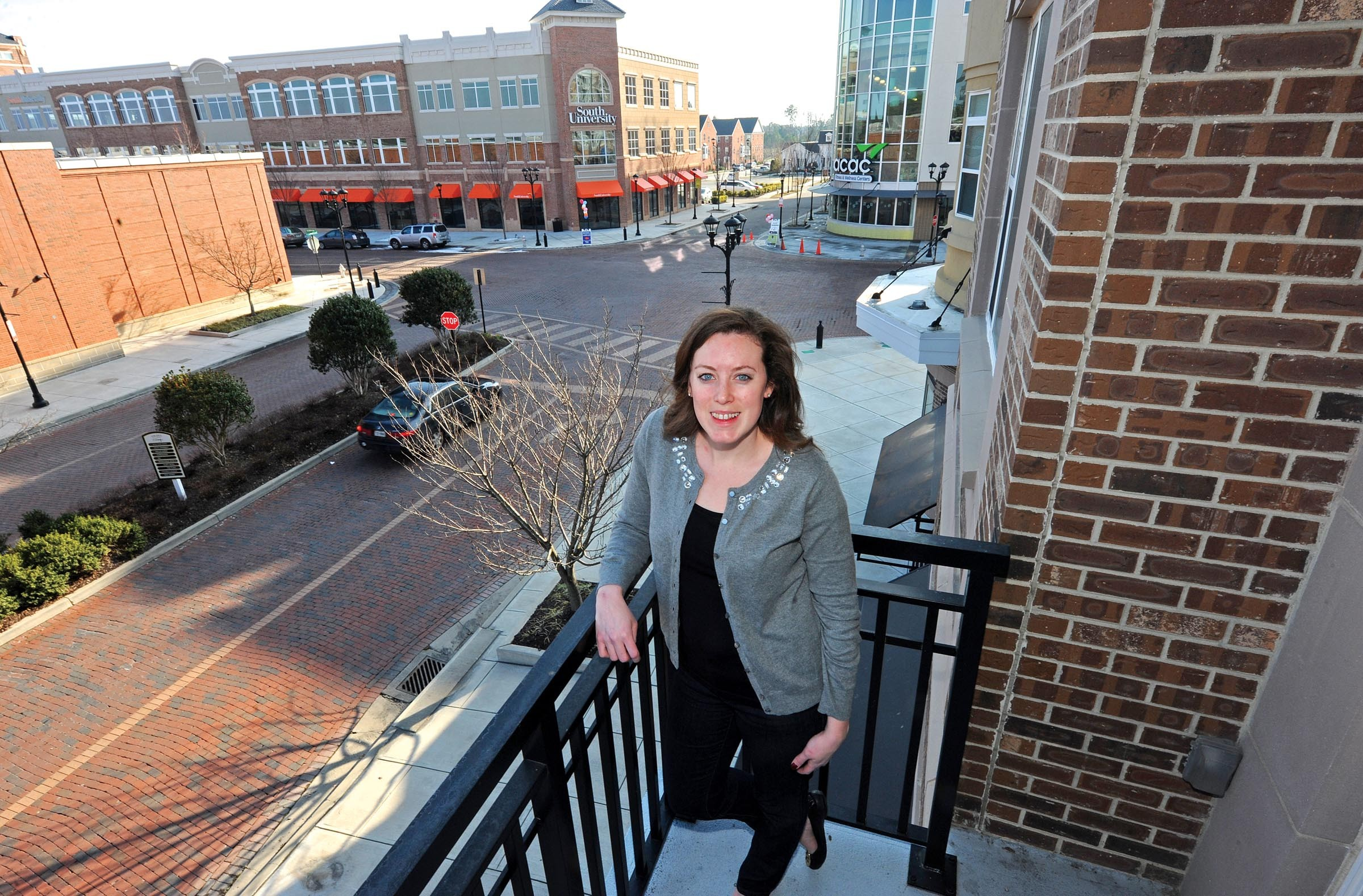 Katelyn Melo, who commutes daily to her job downtown from West Broad Village, relaxes on the balcony of her apartment overlooking Gathering Place. - SCOTT ELMQUIST