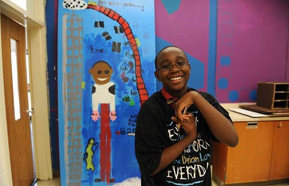 "KeShawn Brooks stands in front of ""D'Moon,"" a self-portrait he created at Art 180.   ""When I paint, the colors talk to me,"" the 11-year-old budding artist says. ""This painting is a way to introduce myself to other people. I want to be an inventor and create stuff for the world."" - SCOTT ELMQUIST"