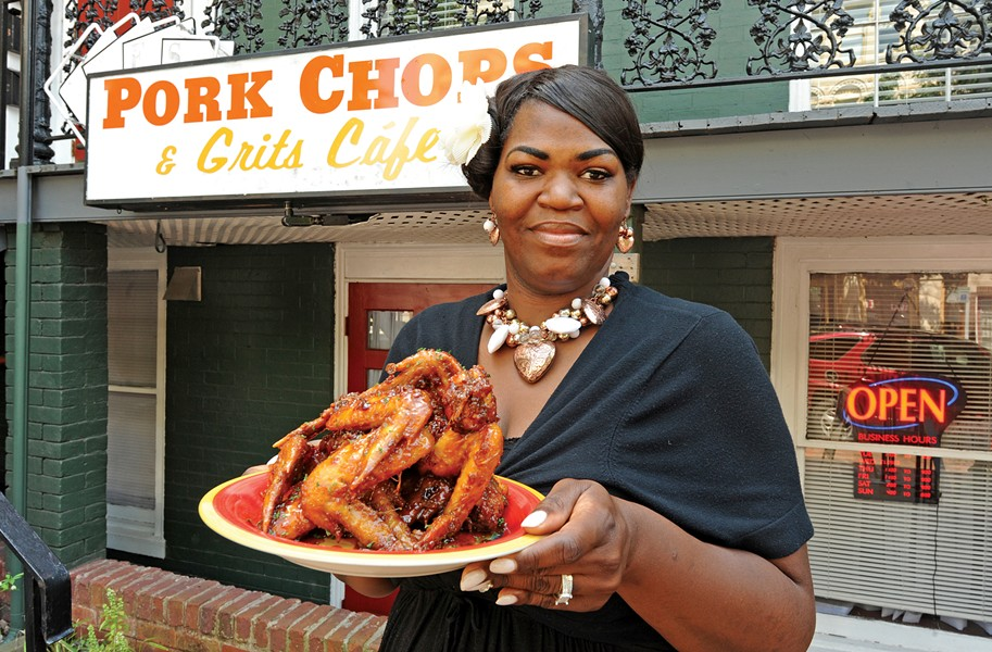 Lady D. Kindle shows off the orange-glazed fried chicken at Pork Chops & Grits Cafe in Jackson Ward. - SCOTT ELMQUIST