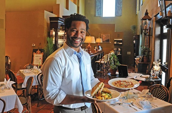 Lamone Waller, general manager of C Street, serves a bacon, arugula and pimento cheese sandwich on sourdough bread with seasonal fruit, and a carbonara pizza, in the welcoming Carytown space. - SCOTT ELMQUIST