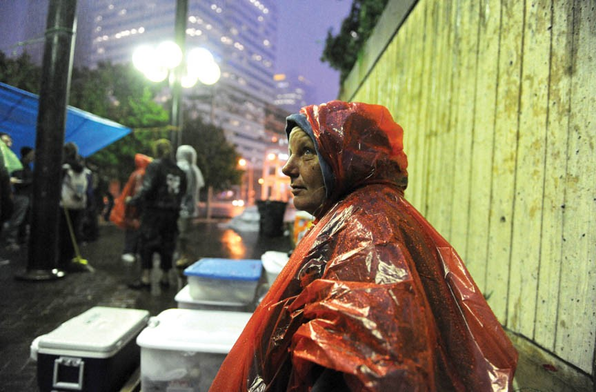 Linda Woodward, one of dozens of homeless people sharing space at Kanawha Plaza with Occupy Richmond protestors, endures the drizzle outside the food tent. - SCOTT ELMQUIST