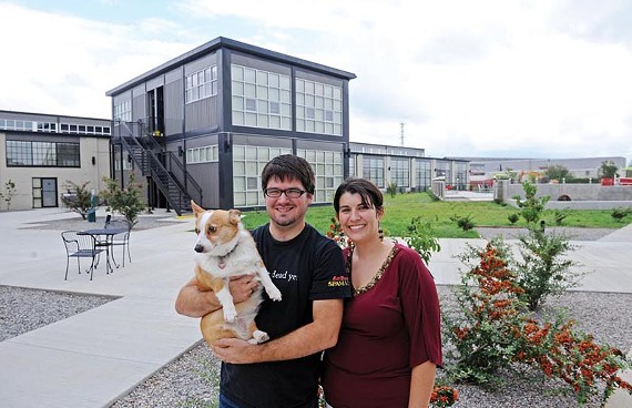 M. Scott Ford, Andrea Goulet and their corgi, Einstein, live and work in the New Manchester Flats. Here, they stand in the complex's central courtyard. - SCOTT ELMQUIST