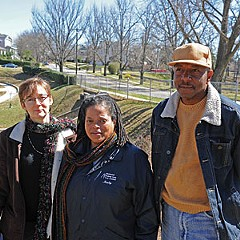 Members of the Friends of Battery Park (from left: Ginnie Morrow, Marilyn Bowman and William Harden) stand in the park near a patch of brush that used to be lined with trees. Photo by Scott Elmquist.