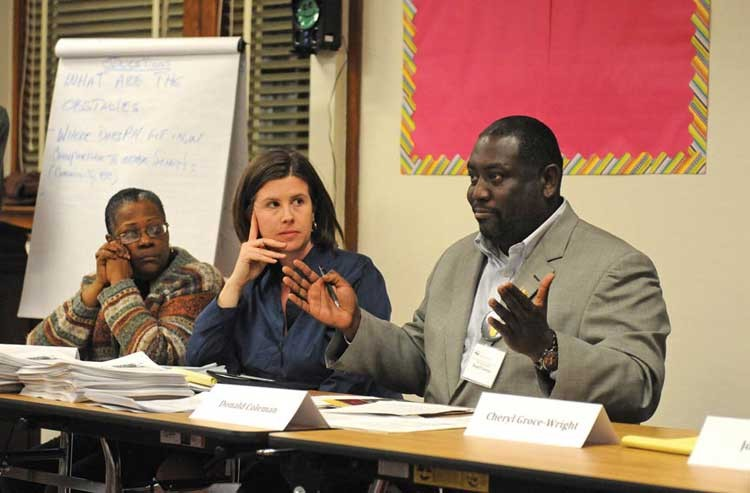 Members of the Patrick Henry board of directors, Sharon Burton and Kristen Larson, listen to Don Coleman, a member of the Richmond School Board, explain the absence of his colleagues at a February meeting of the school's PTA. - SCOTT ELMQUIST