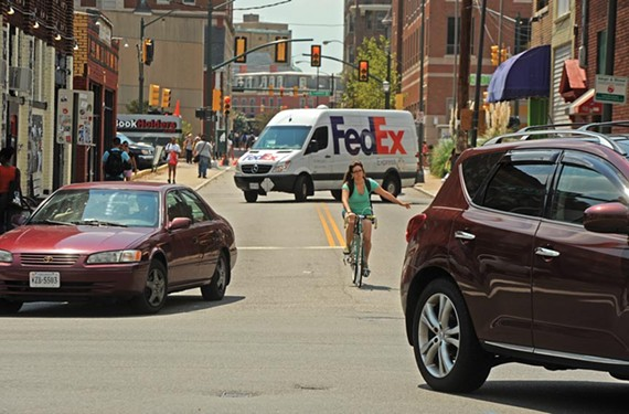 No. 1 Share the road. A bicyclist signals a left turn at the intersection of Laurel and West Broad streets. - SCOTT ELMQUIST
