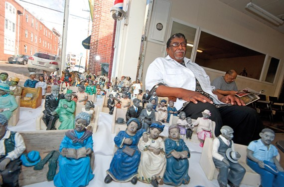Passersby are always stopping at the window of RJ's Barber Shop, where Master Barber Roy Spratley displays the many ceramic figures of churchgoers that customers have given him during the last 15 years.