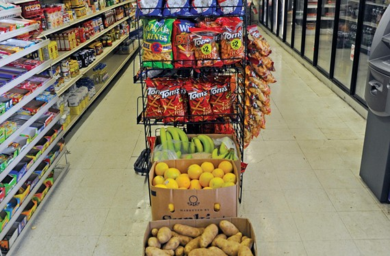 Potatoes, oranges and bananas sit below a display of chips and popcorn at the Clay Street Market in Church Hill.