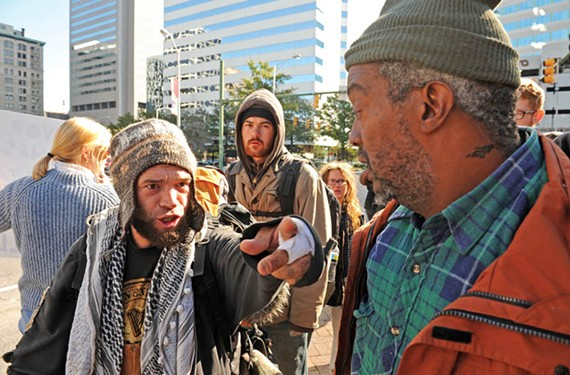 Protestor Al-Alee Khan Al-Wick, left, rails against the police Monday after officers and city workers razed the encampment. - SCOTT ELMQUIST