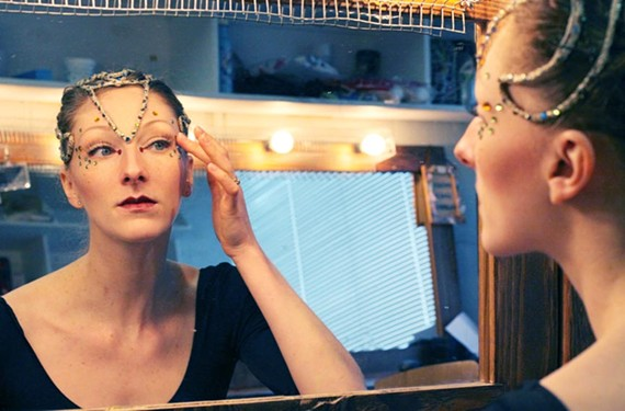 "Richmond Ballet dancer Lauren Fagone applies jewels to her face while preparing her makeup for the role of the Snake in ""The Nutcracker."""