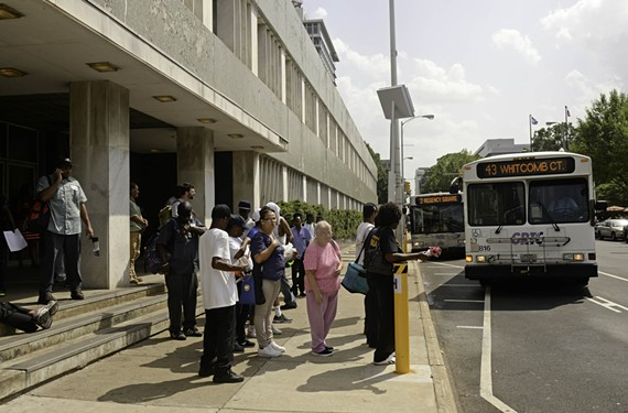Riders line up at the temporary bus transfer plaza downtown, which has come under fire for its long wait times and poor conditions.