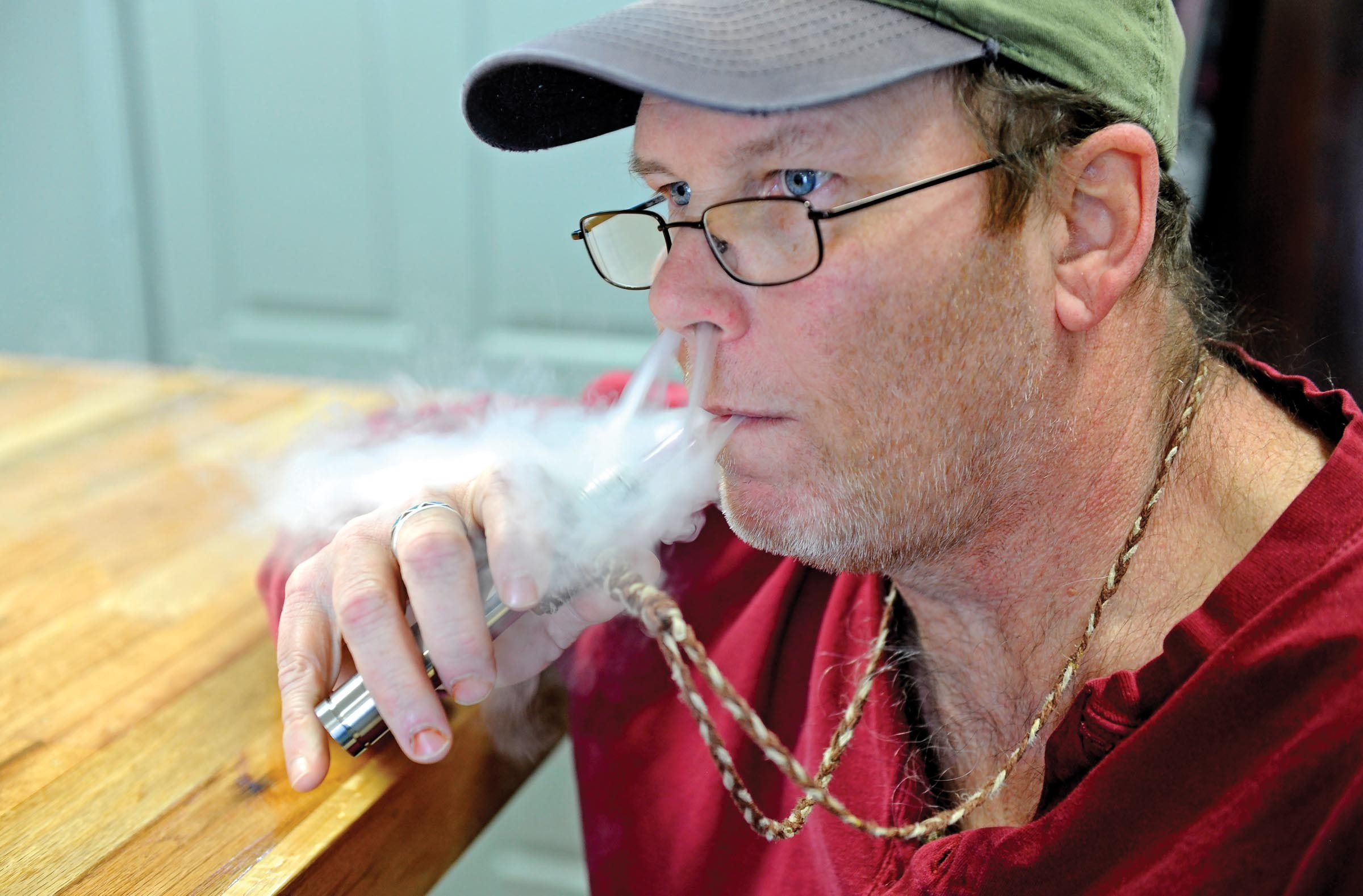RVA Vapes customer David Payne, once a smoker of Swisher Sweets, puffs on a pineapple-upside-down-cake-flavored e-cig. - SCOTT ELMQUIST