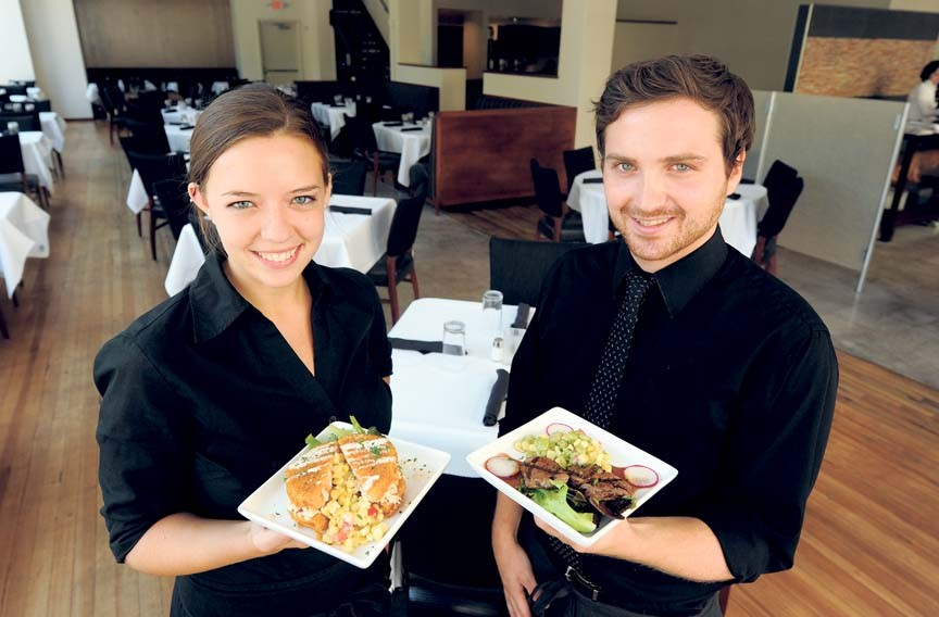 Servers at this downtown newcomer show some of its offerings: Bailey Brunick, left, with the fried green tomato napoleon and Tyler Williams with grilled beef medallions. - SCOTT ELMQUIST