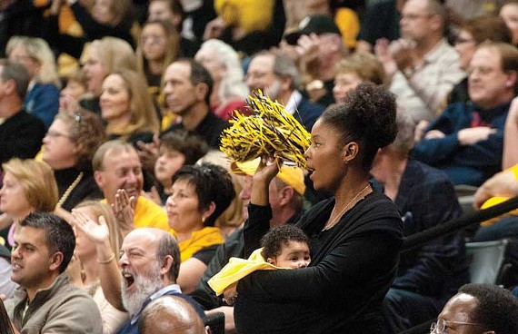Shaka Smart's wife, Maya, holds their new baby girl, Zora, at the Siegel Center on Dec. 9.
