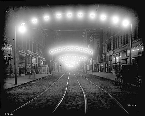 """Shot in Norfolk, photographer Harry Mann's """"Night View ...  Along Granby Street"""" (1914) is one of many pieces of night photorgaphy that beg imaginative narrative from the viewer."""