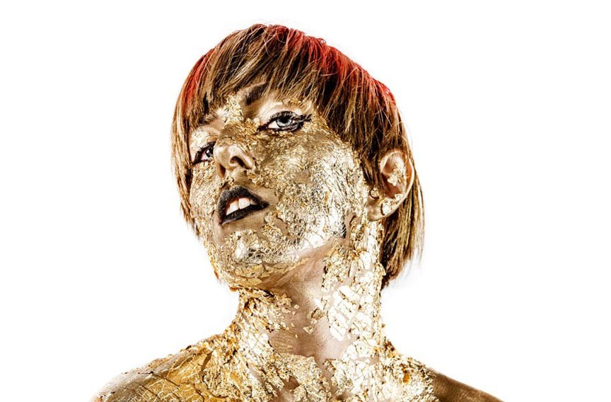 Singer Meghan Remy (U.S. Girls) is covered in gold flake by Canadian visual artist and fashion designer Renata Morales (Arcade Fire).