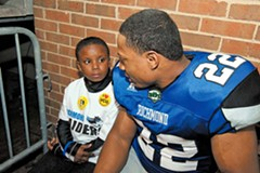 Stephen Cason, a defensive back from William and Mary, sits with Genesis Toliver Jr., a child he's mentoring, on the sidelines at the end of the April 16 game against Fayetteville. The Raiders won, 61-43. - SCOTT ELMQUIST