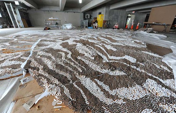 Summer and smoke: Workers in a parking garage painstakingly turn 500,000 cigarettes into a 40-by-18-foot tiger carpet. - SCOTT ELMQUIST