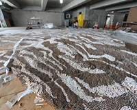 Summer and smoke: Workers in a parking garage painstakingly turn 500,000 cigarettes into a 40-by-18-foot tiger carpet.