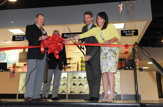 The attorney general helps cut the ribbon at the grand opening of Colonial Shooting Academy in the West End in April. - SCOTT ELMQUIST
