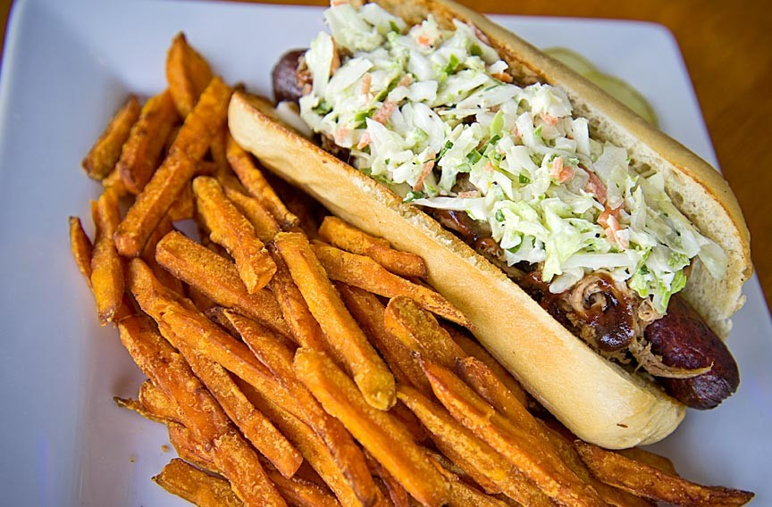 The bacon-wrapped, deep-fried jumbo hot dog at the new Hogshead Cafe is topped with pulled pork barbecue, sauce and slaw. - ASH DANIEL