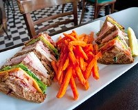 The Devil's Triangle club sandwich is served with sweet potato fries at the neighborhood's revamped hangout, the Franklin Inn.