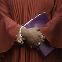 Scenes From the Vigil for Kiarri Edwards The hands and purple bible of the Rev. Rosalind Battle, who offered a prayer during the service. Scott Elmquist