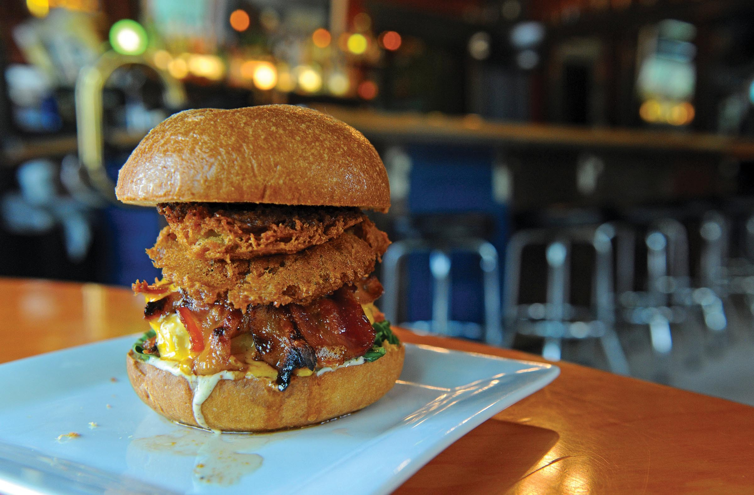 The Henry Bain burger at the Well puts an onion ring on brioche to heighten the experience. - SCOTT ELMQUIST