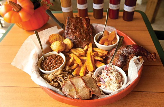 The Hog Wild platter, intended to serve two or three people, has a pound of ribs, half a chicken, choice of smoked meat and corn bread, fries, beans, apples and slaw. - SCOTT ELMQUIST
