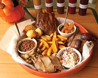 The Hog Wild platter, intended to serve two or three people, has a pound of ribs, half a chicken, choice of smoked meat and corn bread, fries, beans, apples and slaw.