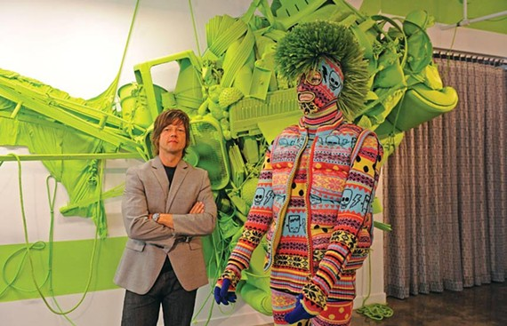 """The Martin Agency's John Norman poses with """"Scare Isle Knit Monster,"""" a colorful work created by London's Sibling fashion collaborative. Get an eyeful while you can — the company's new gallery will not be open to the general public. - SCOTT ELMQUIST"""