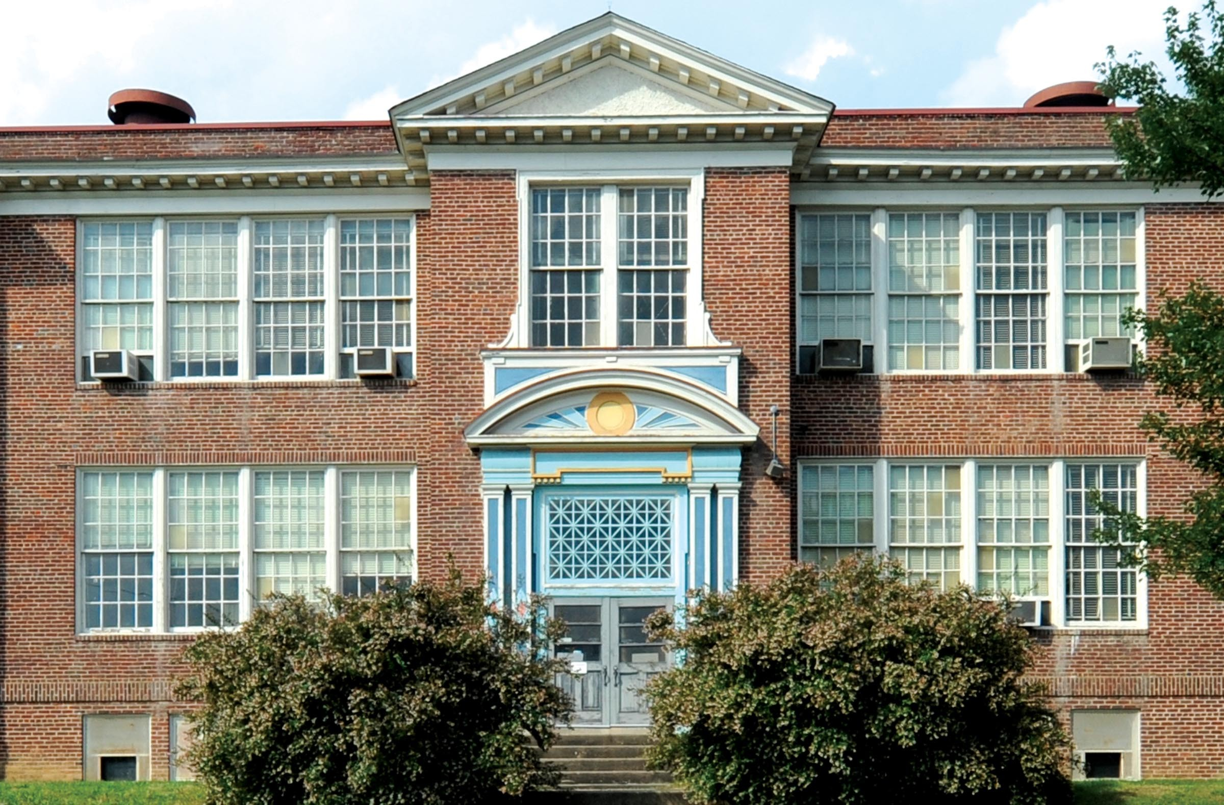 The schools original east wing, built in 1917, features a rounded pediment over its entryway. - SCOTT ELMQUIST