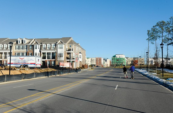 Two boys skateboard on Liesfeld Parkway while house construction in West Broad Village continues nearby. - SCOTT ELMQUIST