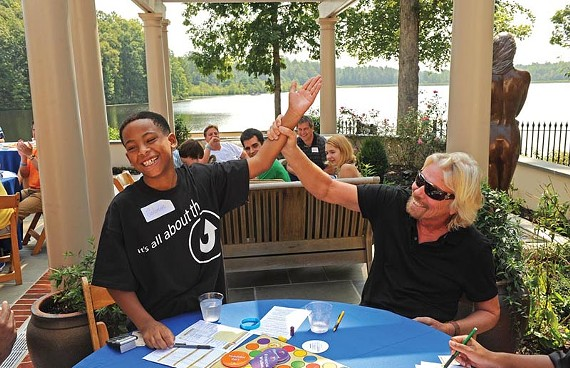 Two men who are good with money: Sir Richard Branson congratulates Solomon Dortch, 11, on winning a financial-education board game. - SCOTT ELMQUIST