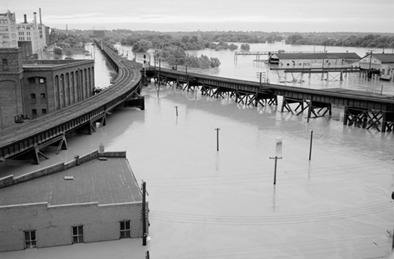Flooding in Shockoe Bottom. This area was also flooded during Hurricane Gaston in 2004. The Bottom's Up Pizza Building is visible in the bottom left corner. - THE LIBRARY OF VIRGINIA