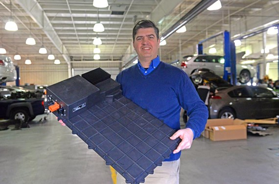 Steve Cummings, senior manager for marketing and strategy at Evatran, holds a module that will fit on the underside of a Chevrolet Volt. When the car-mounted module gets close to another embedded at the car owner's home, the car will recharge wirelessly. - SCOTT ELMQUIST