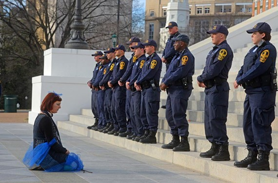 Suzanne Shaver of Richmond kneels before state police at the anti-Dominion protest in February. - SCOTT ELMQUIST