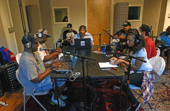 Marc Cheatham sits at the head of the table during his Cheats Movement podcast, which recently celebrated its first anniversary. On Saturday, Sept. 17, Cheatham will take part in the Afrikana Film Festival moderating a discussion with a Duke University professor and producer, 9th Wonder. - SCOTT ELMQUIST