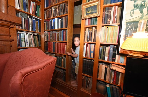 John Lee Worsham, 3, the sixth generation of his family to live in the 102-year-old house, demonstrates the sliding bookcase that provides a secret escape from the library. - SCOTT ELMQUIST