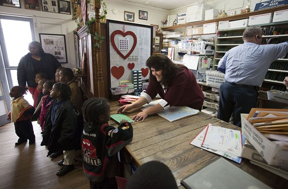 Postmaster Kathy Fajna helps youngsters mail their Valentine's cards. They were on a field trip from their Gaston, N.C., elementary school - BILL TIERNAN