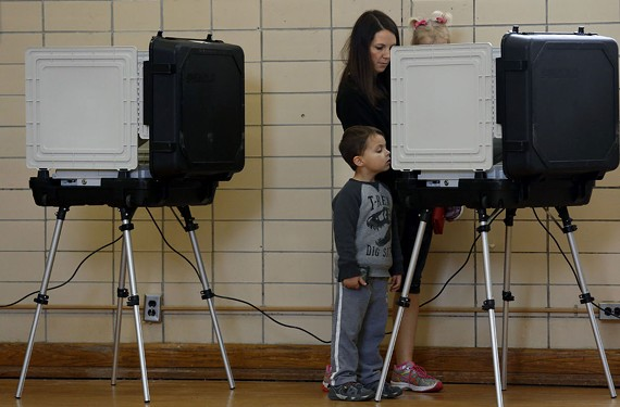 Owen Guirlinger, 4, watches his mother Amy Guirlinger cast her votes while holding her 2-year-old daughter Anna at Granby Elementary School in Norfolk. - THE' N. PHAM