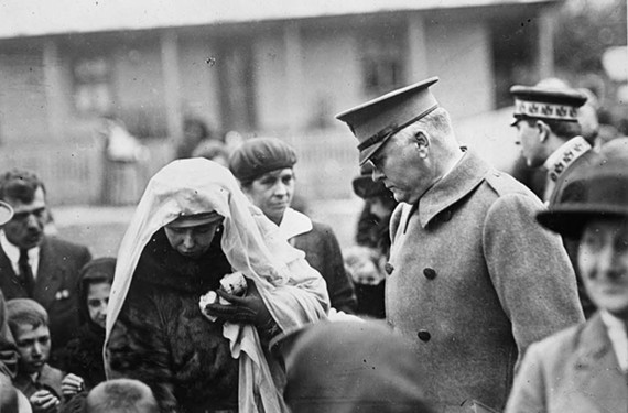 Queen Marie hands out American-made biscuits to children as Col. Henry Anderson, the commissioner to the Balkans for the American Red Cross, looks on after World War I. - LIBRARY OF CONGRESS