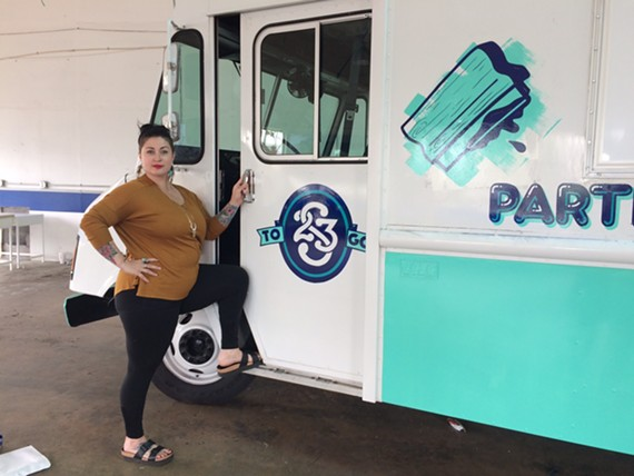 Recent Style Weekly Women in the Arts honoree, Ashley Hawkins stands next to Studio Two Three's new mobile studio, which will be debuting at RVA Earth Day on April 22.