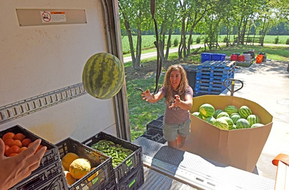 Assistant Farm Manager Seyra Whitney helps to load the back of a truck for delivery. Watermelons have been some of the most popular produce grown at the farm this season. - SCOTT ELMQUIST