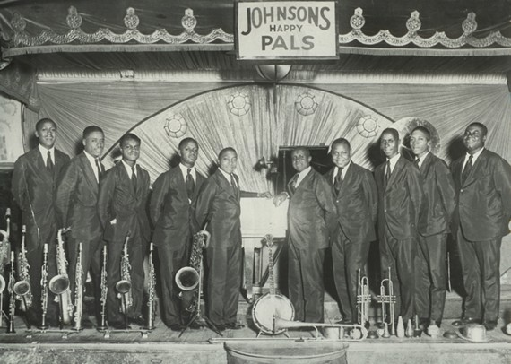 "Roy Johnson's Happy Pals Orchestra at the Savoy Ballroom in New York – 1929. (L to R): Harold ""Pops"" Griffin (clarinet/sax), Emmitt ""Lic"" Johnson (clarinet/sax), Nathaniel ""Buster"" McPherson (clarinet/sax), Roy F. Johnson (drums, leader), Edward ""Pickles"" Humes (trumpet), Leroy ""Fess"" Wyche (piano), Percy Trent (trumpet), Fleming ""Beans"" Edwards (trombone), William ""Mama"" Allen (bass, tuba), Edward ""Skinny"" Trent (banjo)"