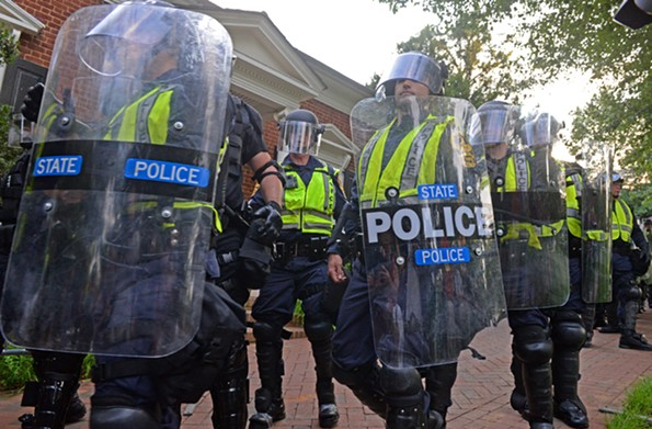 Police in riot gear form a wall after protesters move the rally. - SCOTT ELMQUIST
