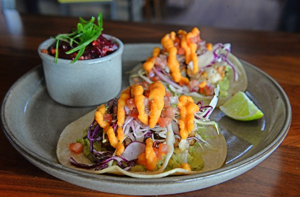 The grilled Gulf shrimp tacos feature a house dry rub, guacamole, cured cabbage, pico de gallo and papaya hot sauce served on two corn tortillas. - SCOTT ELMQUIST